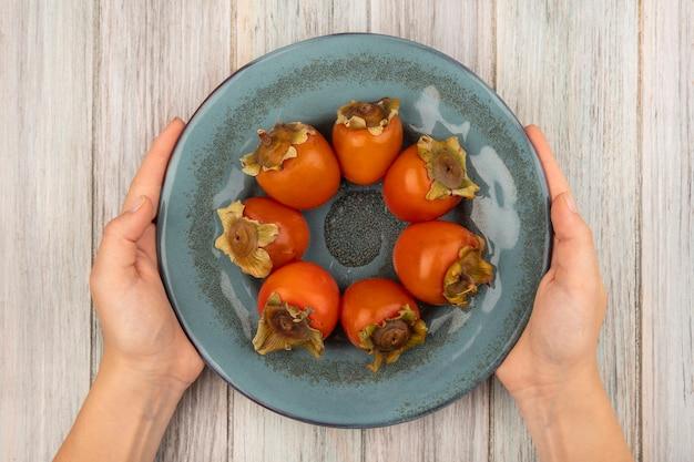 Vista superior de mãos femininas segurando um prato de caquis frescos e doces em uma superfície de madeira cinza