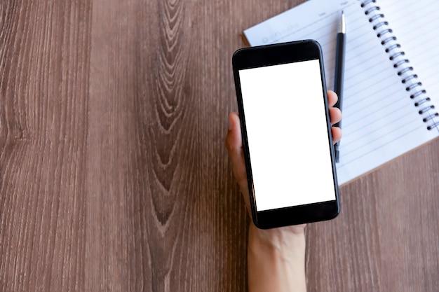 Vista superior de mãos femininas segurando um telefone inteligente com tela branca em branco