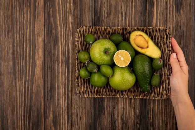 Vista superior de mãos femininas segurando uma bandeja de vime com frutas frescas, como maçãs verdes e limas feijoas em uma parede de madeira com espaço de cópia