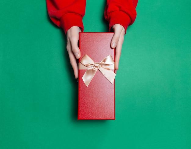 Vista superior de mãos femininas segurando uma caixa de presente na superfície da cor verde