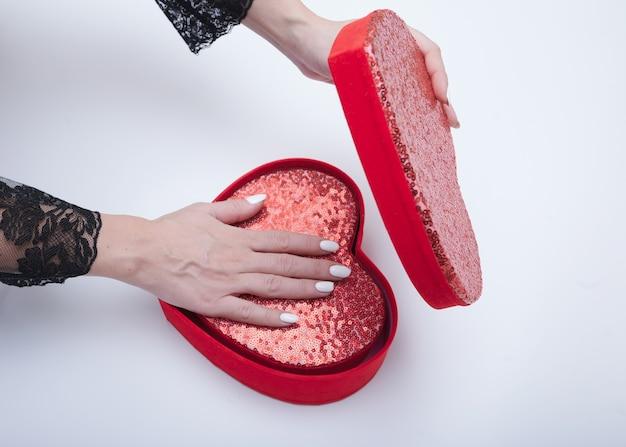 Vista superior de mãos femininas segurando uma caixa de presente vermelha aberta em fundo branco