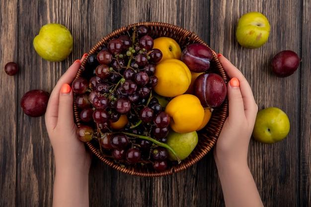 Vista superior de mãos femininas segurando uma cesta de frutas como pluot de damasco de uva em fundo de madeira