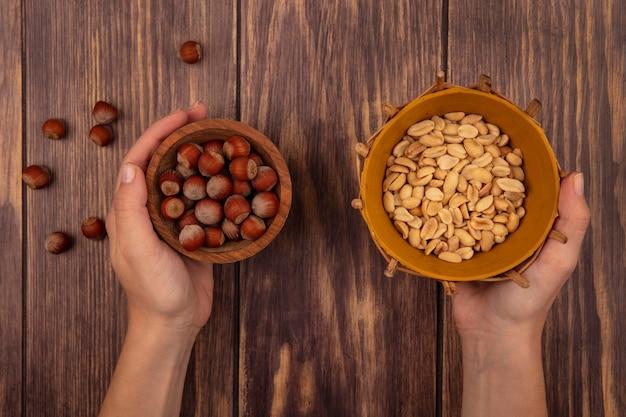 Vista superior de mãos femininas segurando uma tigela de madeira com amendoim e amendoim em um balde na parede de madeira