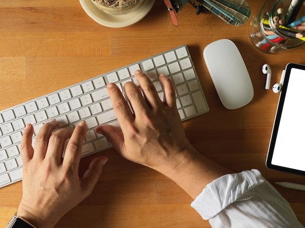 Vista superior de mãos masculinas digitando no teclado do computador com suprimentos na mesa de madeira