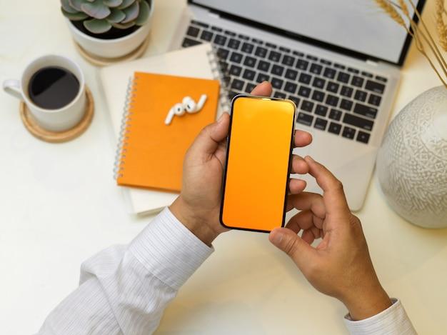 Vista superior de mãos masculinas trabalhando em smartphone na área de trabalho criativa com laptop, notebooks e xícara de café