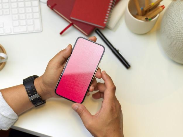 Vista superior de mãos masculinas usando smartphone na área de trabalho com artigos de papelaria e suprimentos