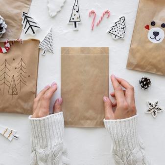 Vista superior de mãos preparando sacolas de natal