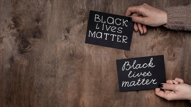 Vista superior de mãos segurando cartas de matéria de vidas negras com espaço de cópia