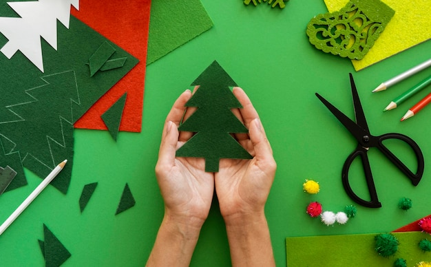 Vista superior de mãos segurando uma árvore de natal feita de papel