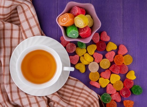 Vista superior de marmeladas e xícara de chá em pires no pano xadrez e fundo roxo