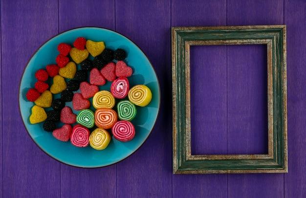 Vista superior de marmeladas no prato e moldura em fundo roxo com espaço de cópia
