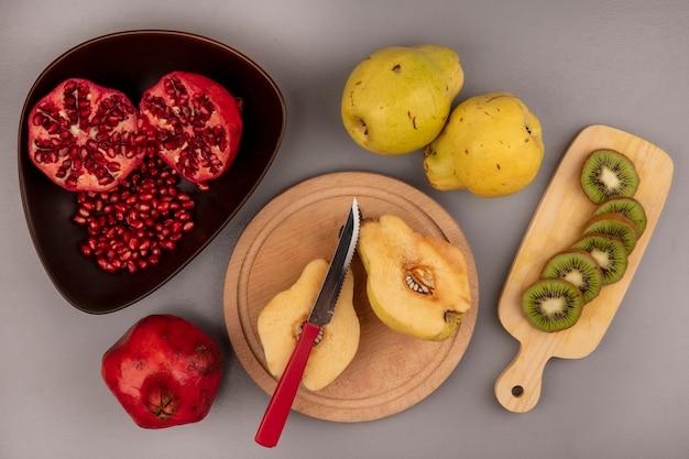 Vista superior de marmelos frescos cortados ao meio em uma placa de cozinha de madeira com romãs em uma tigela com fatias de kiwi em uma placa de cozinha de madeira