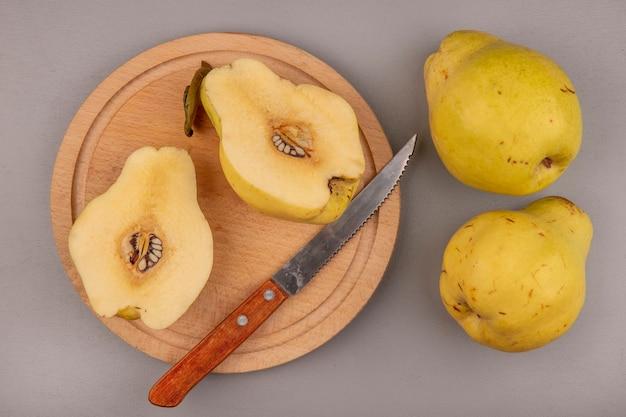 Vista superior de marmelos frescos cortados ao meio em uma placa de cozinha de madeira com uma faca com marmelos inteiros isolados