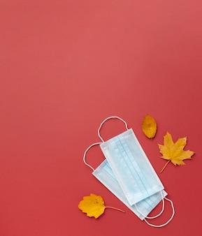 Vista superior de máscaras médicas com folhas de outono e espaço de cópia