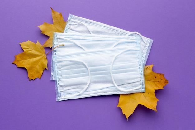 Vista superior de máscaras médicas com folhas de outono