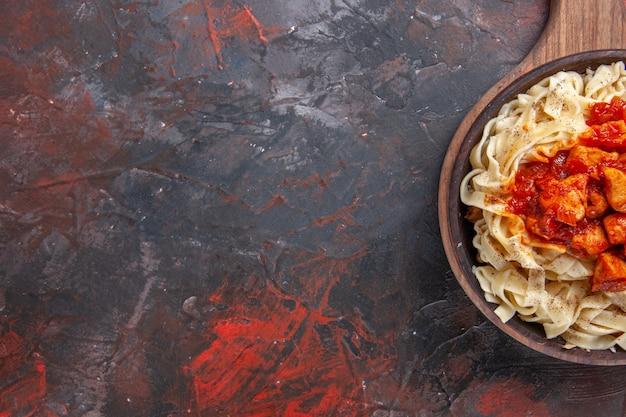 Vista superior de massa cozida com molho de carne em um prato de massa escura de massa escura