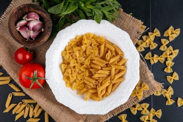 Vista superior de massa crua em um prato com tomate, alho e um punhado de hortelã em um guardanapo bege