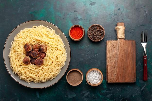 Vista superior de massa italiana cozida com almôndegas e temperos em mesa azul escura
