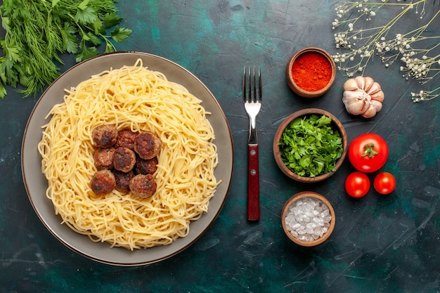 Vista superior de massa italiana cozida com almôndegas e verduras em superfície azul escura