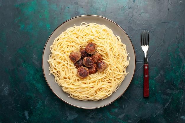 Vista superior de massa italiana cozida com almôndegas na superfície azul escura