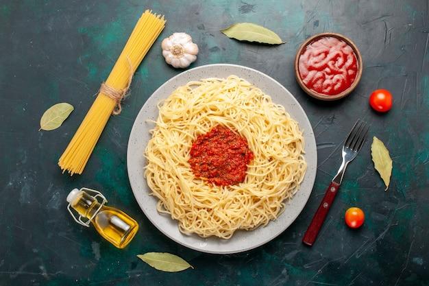 Vista superior de massa italiana cozida com carne de tomate picada na mesa azul escura