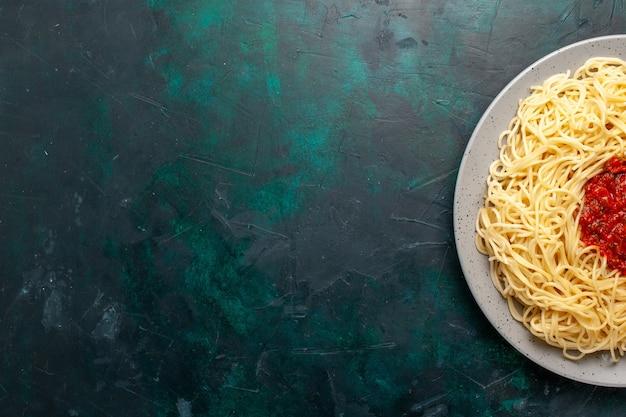 Vista superior de massa italiana cozida com carne picada e molho de tomate na mesa azul escura