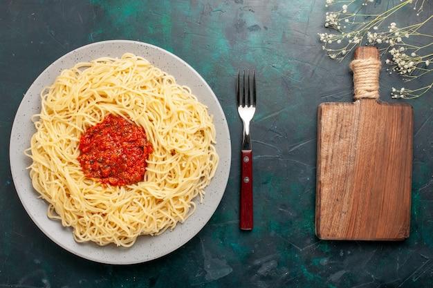 Vista superior de massa italiana cozida com carne picada e molho de tomate na superfície azul escura