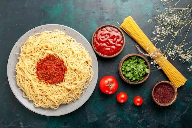 Vista superior de massa italiana cozida com carne picada, molho de tomate e temperos em superfície azul escura