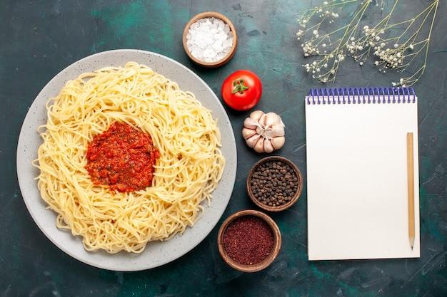 Vista superior de massa italiana cozida com carne picada, molho de tomate e temperos na mesa azul