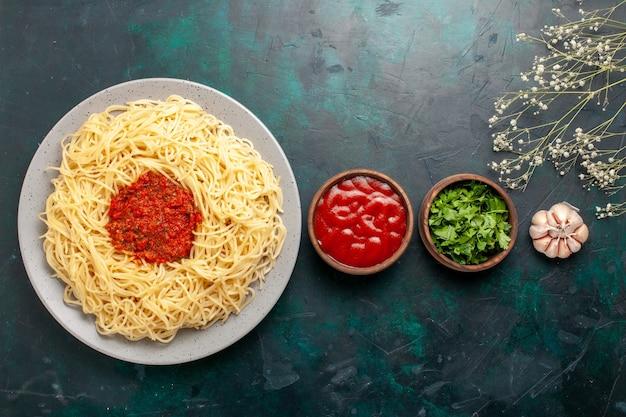 Vista superior de massa italiana cozida com carne picada, molho de tomate e temperos na superfície azul
