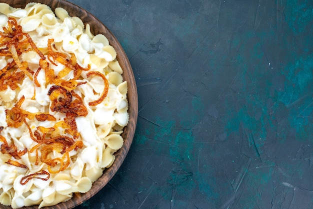 Vista superior de massa italiana cozida com cebola frita no azul