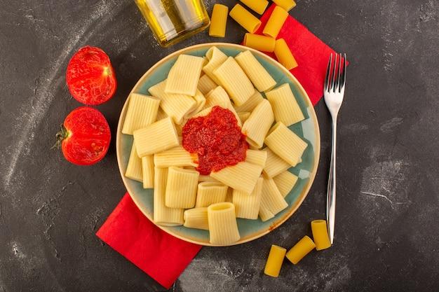 Vista superior de massa italiana cozida com molho de tomate dentro de prato com azeite de oliva