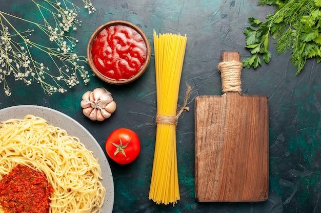 Vista superior de massa italiana cozida com molho de tomate e carne picada na mesa azul