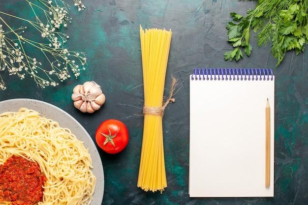 Vista superior de massa italiana cozida com molho de tomate e carne picada na superfície azul