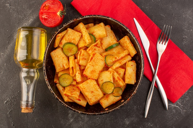 Vista superior de massa italiana cozida com molho de tomate e pepino dentro da panela