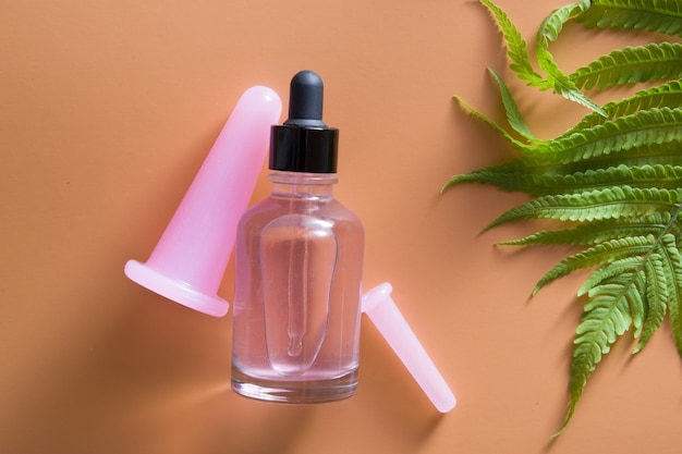 Vista superior de massageadores faciais a vácuo e frasco conta-gotas de óleo com folhas de samambaia