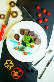 Vista superior de medalhões grelhados de carne com tomate cereja e molho num prato