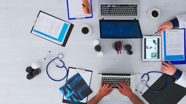Vista superior de médicos residentes aconselhando um médico usando videochamada, sentado na mesa de uma clínica com equipamento médico