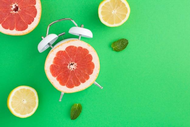 Vista superior de meia toranja no mostrador do despertador e frutas frescas fatiadas