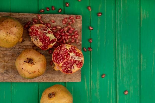 Vista superior de meias-romãs frescas em uma placa de cozinha de madeira com sementes isoladas em uma superfície de madeira verde com espaço de cópia