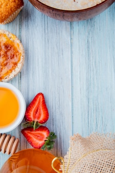 Vista superior de meio corte morangos com aveia estaladiço xarope de pêssego manteiga de cupcake na madeira com espaço de cópia