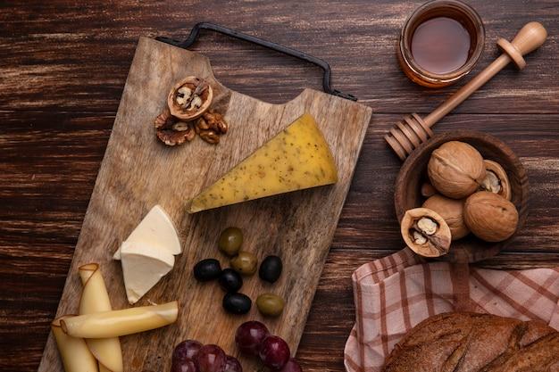 Vista superior de mel em uma jarra com nozes e um pedaço de pão preto com variedades de queijos e uvas em um suporte sobre um fundo de madeira