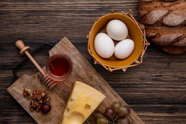 Vista superior de mel em uma jarra com queijo e nozes em um carrinho com ovos de galinha e pão preto em um fundo de madeira