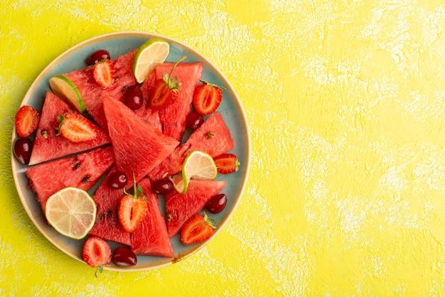 Vista superior de melancia fatiada com morango em fatias de limão na superfície amarela