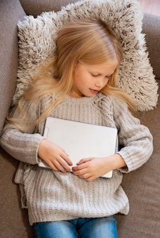Vista superior de menina dormindo com tablet