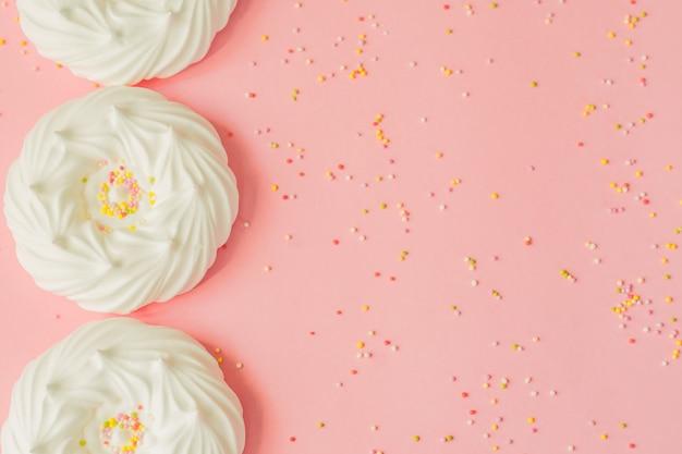 Vista superior de merengues de ar branco caseiro e decorações de confeitaria em rosa