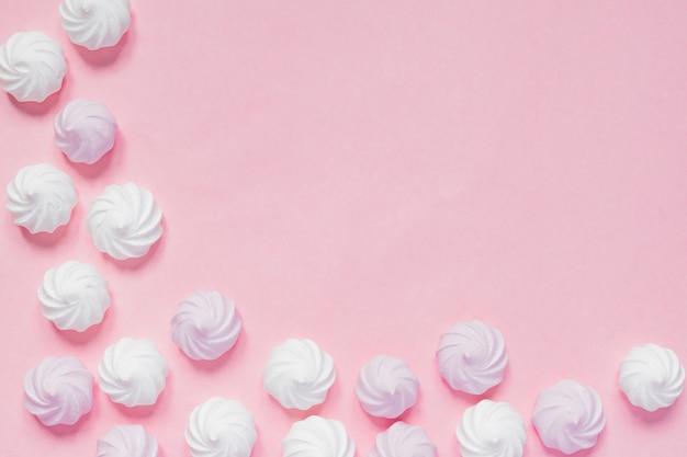 Vista superior de merengues torcidos brancos e rosa em fundo rosa