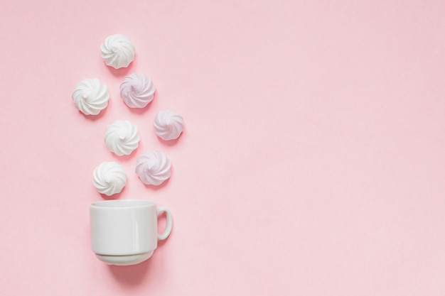 Vista superior de merengues torcidos brancos e rosa em rosa