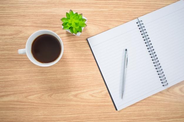 Vista superior de mesa com cadernos, canetas, café e vasos de flores. fundo.