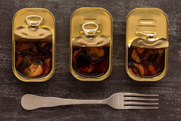 Vista superior de mexilhões preservados em latas com garfo
